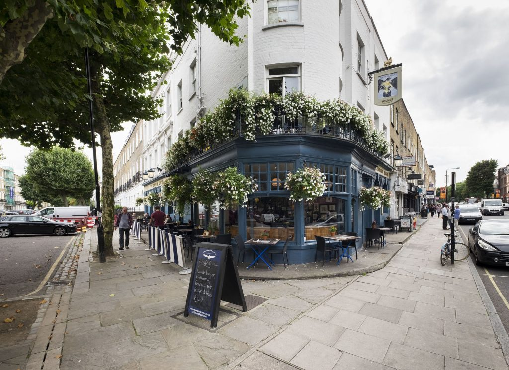 The front window of a traditional corner pub. The pub has large glass windows, blue wood panels and hanging baskets with beautiful white flowers