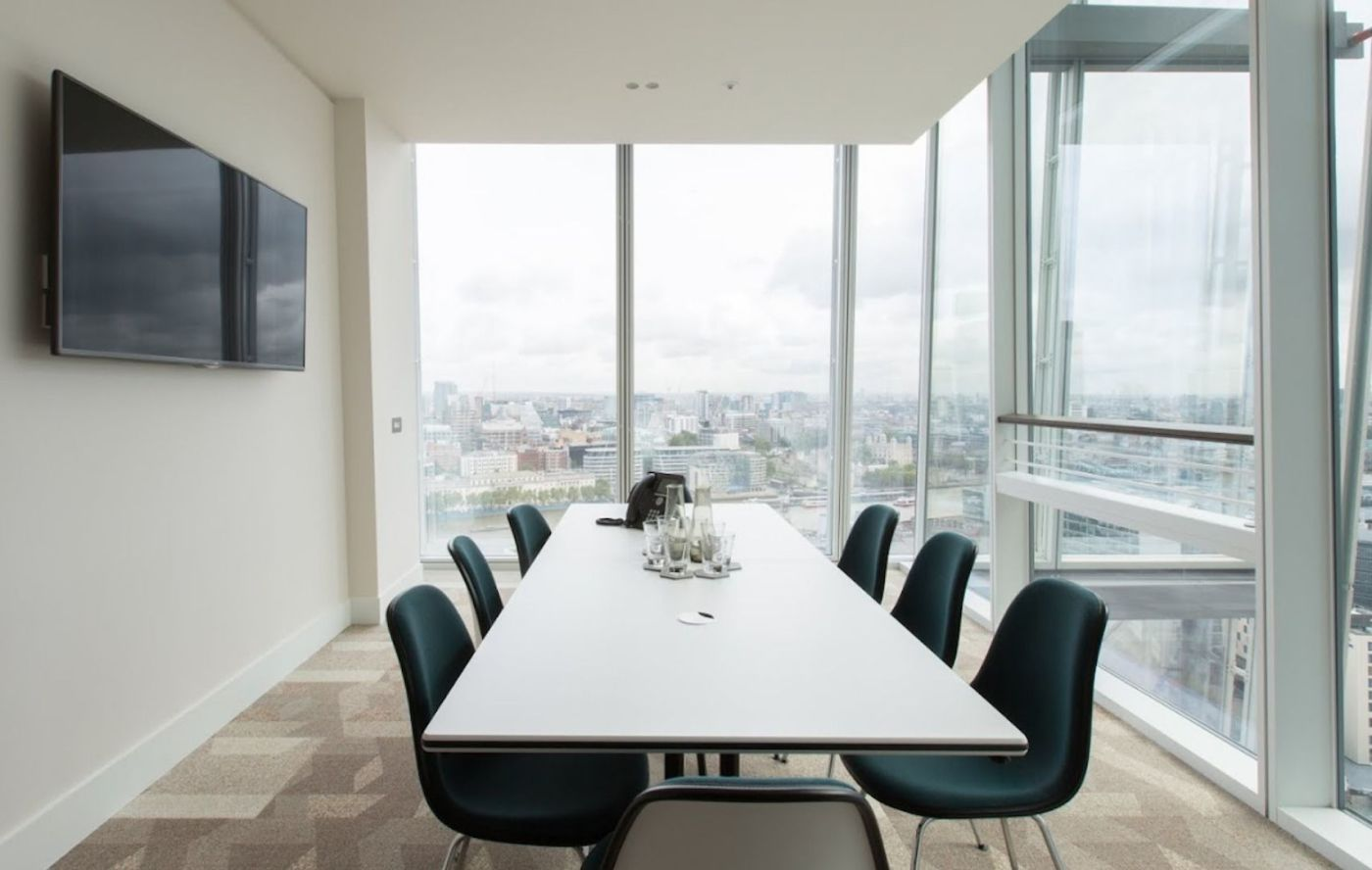 A meeting room with two glass walls and a long table with 6 black chairs
