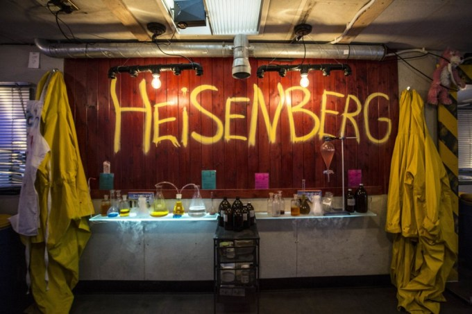 A wooden wall reads Heisenberg written in yellow spray paint across it. There are two yellow lab coats hanging from the wall and science equipment running along the top of the bar.