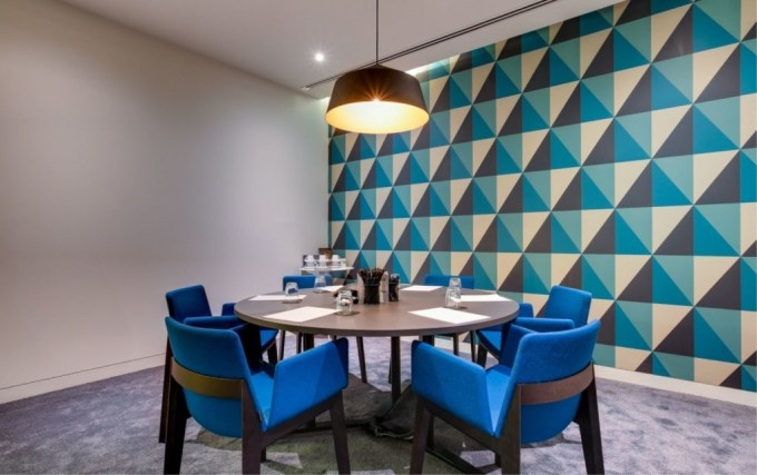 Meeting Room 4, The Clubhouse, a meeting room with one wall decorated in a abstract blue, black and cream pattern. There is a small brown table in the centre of the room with blue chairs surrounding it.