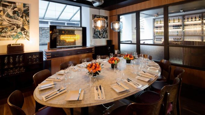 Private Dining Room, Heddon Street Kitchen is a small private dining room with a marble table in the centre of the room surrounded by brown wooden chairs. There are orange flowers arranged in the centre of the table as well as napkins and cutlery laid out for a meal.