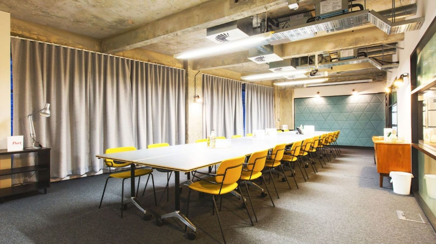 A large meeting room with yellow chairs and concrete walls