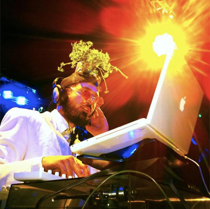 A bearded male DJ wearing headphones, a hat sprouting flowers and red tinted round glasses is looking at a white laptop with one hand on his ear listening to music