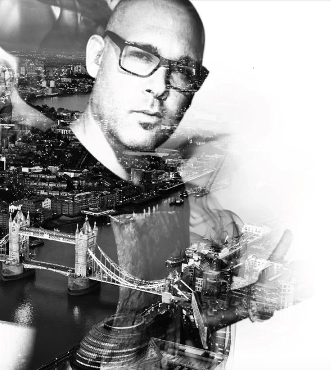 black and white photo of a bald man wearing glasses and a black t-shirt layered over the top of a black and white aerial photo of tower bridge