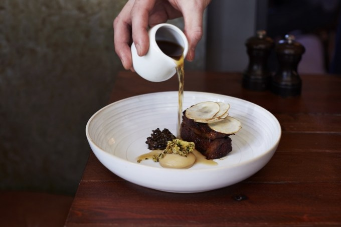 hand pours sauce onto gourmet food
