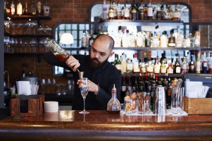 bartender pours spirit into measurement cup