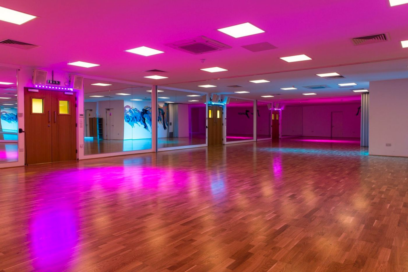 Large dance studio with mirror lining one wall and pink mood lighting.