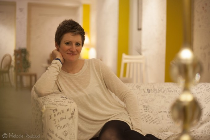 a woman sitting on a sofa that is covered in hand written notes