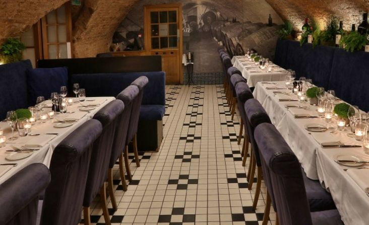 A restaurant in an arched lower ground floor venue. With long tables and a brick ceiling.