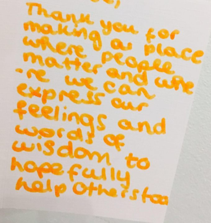 a close up shot of a message written on a wall with orange pen the message reads 'thank you for making a place where people matter and where we can express our feelings and words of wisdom to hopefully help others too'