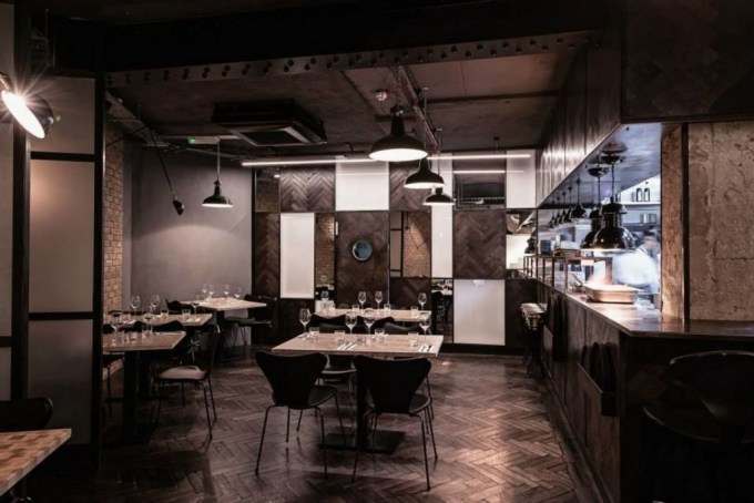 Restaurant Four to Eight. Dark stylish room with a counter looking into the kitchen. The walls and ceiling are brown and grey and tables and chairs are arranged within the space