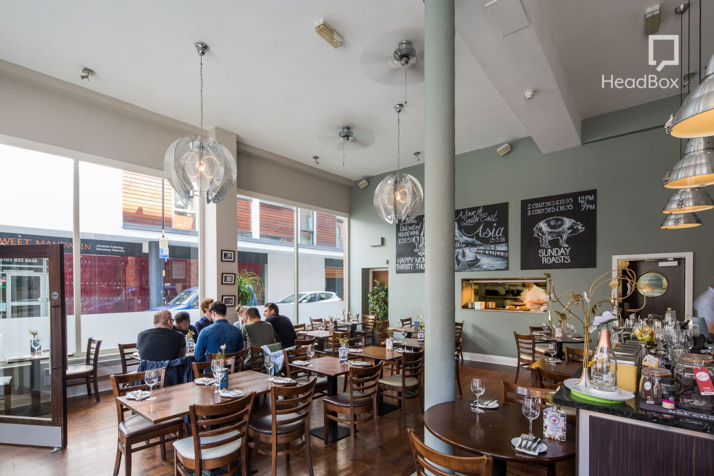 An open plan Manchester restaurant with dark wooden table and chairs