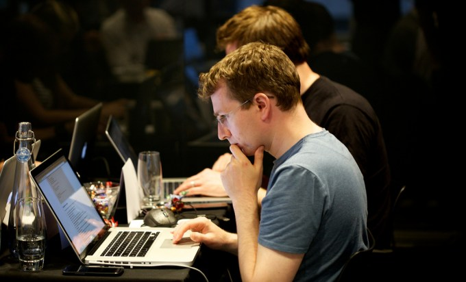 Two men sit side-on at their laptops in the foreground. The closest man has one hand on his chin in thought. The Background is dark and and out of focus but you can see other figures on their laptops too.