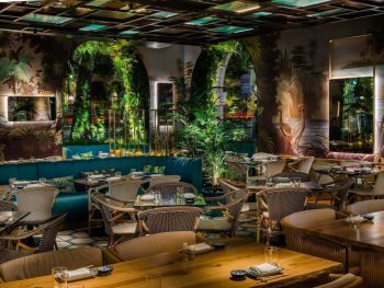 restaurant space with chairs and tables including blue booths, lush plants and animal art