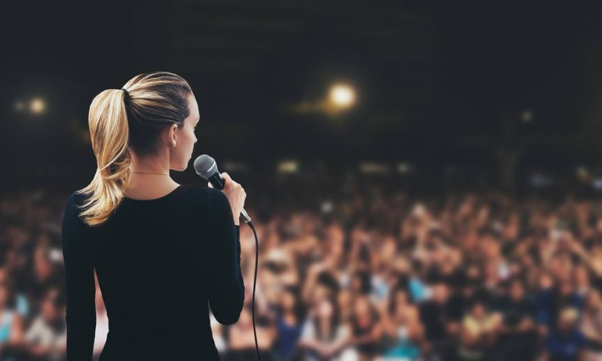 Women speaking with microphone in front of crowd