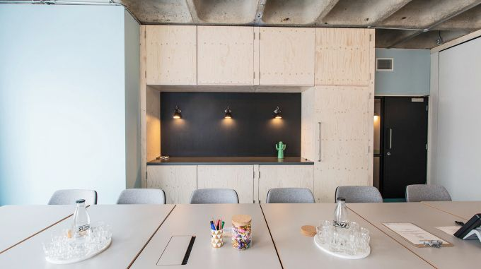 A large meeting table in front of a baby blue wall with pine cupboards