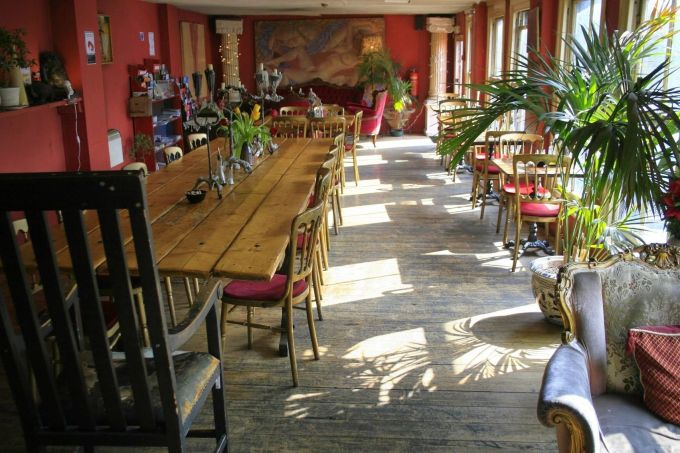 red cafe with plants and tables