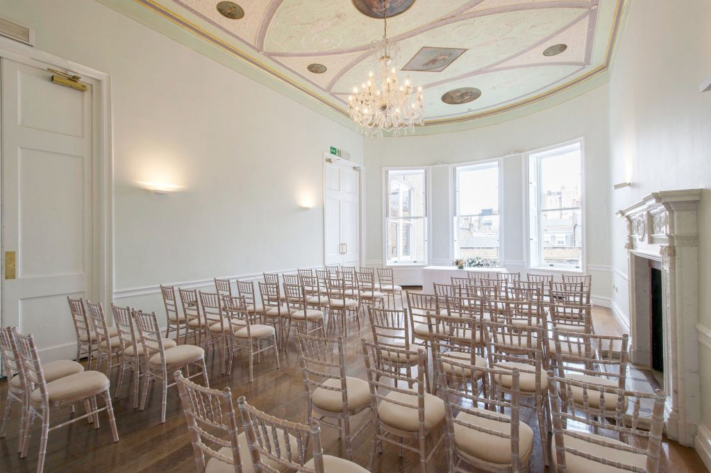 A small light, bright Space with detailed chairs set out in conference style. The space has a small chandelier hanging from the detailed ceiling and has 3 bay windows letting in lots of natural light.