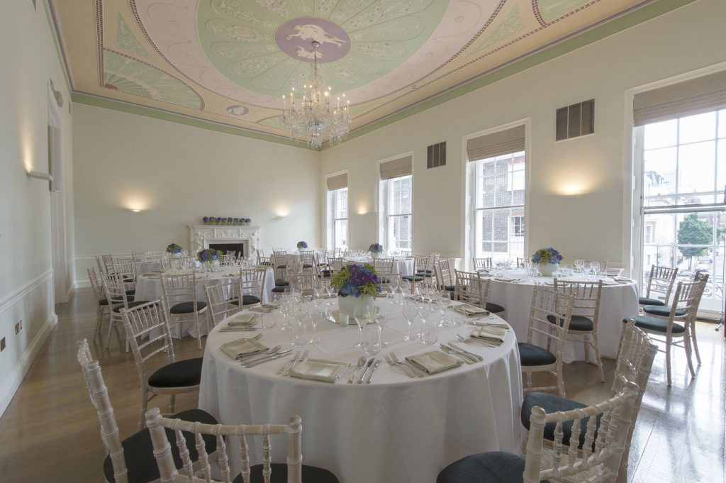 A medium sized room with high ceilings and a chandelier. The room as several large circle dinner tables set for a private party.