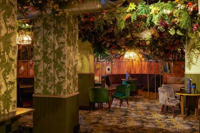 An unusual venue that has fake fauna on the ceiling, velvet chairs and floral wallpaper