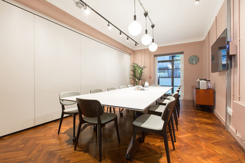 A bright, light meeting room with one large table in the middle.The walls are painted pink and modern exposed lightbulbs hang from the ceiling.