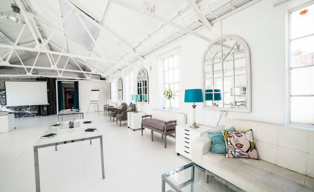 A beautiful white loft open Space with blue furnishings and white leather sofas