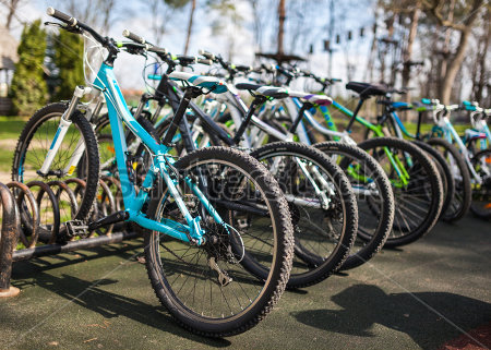 5 or more bikes all lined up on a bike rack, making the top wheels slightly high than the back wheels. In the background is a park with green grass, trees and a blue sky