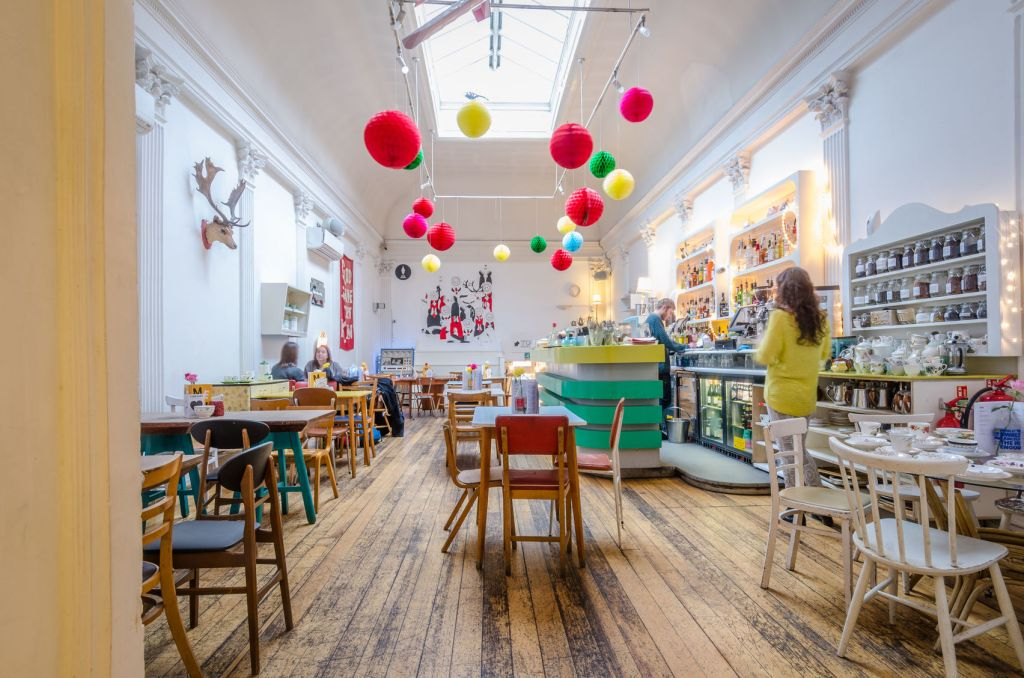 A cafe venue with high ceilings and large coloured balls hanging from the ceiling
