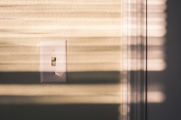 a cream wall with a white light switch
