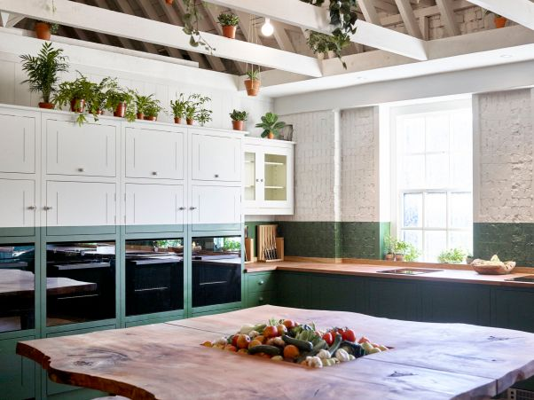 The Bourne and Hollingsworth Kitchen is a home away from home. The large oak island stands int he middle with fresh fruit and veg in the centre and there are kitchen cupboards and ovens on the left hand side.