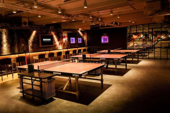 An underground ping pong room that has 3 tables lit up in orange light