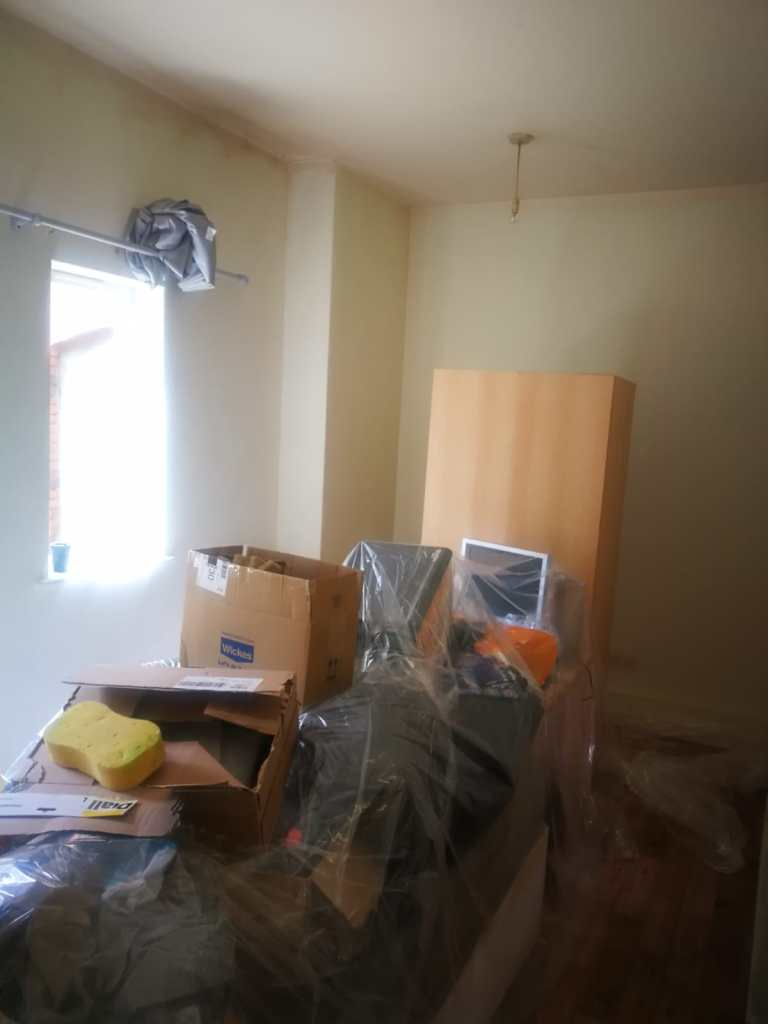 a room with cream walls that look dirty, there is a pile of belongings in the middle covered up with a plastic sheet