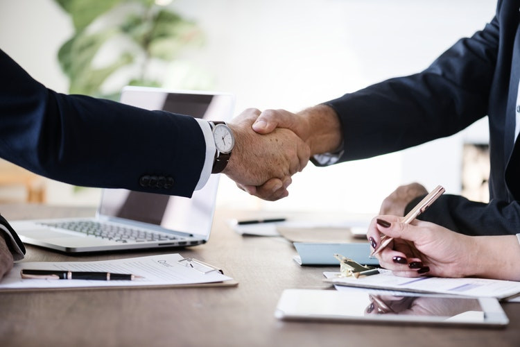 two people shaking hands over the desk
