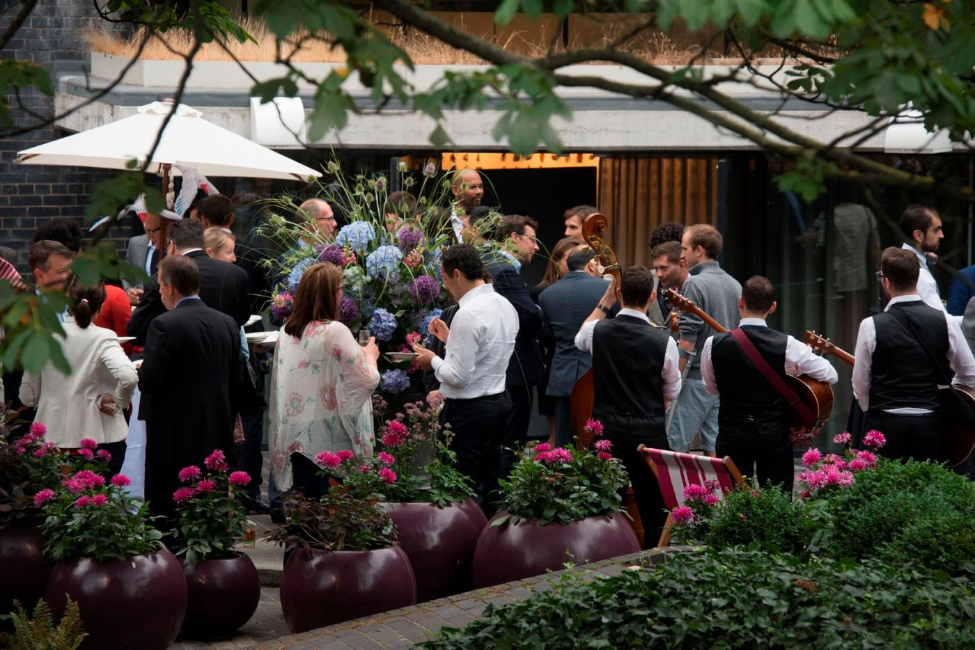 a band are playing in an outdoor terrace area with people networking around them at the museum of london