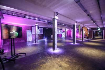 function room with pillars, purple lighting and TV screens
