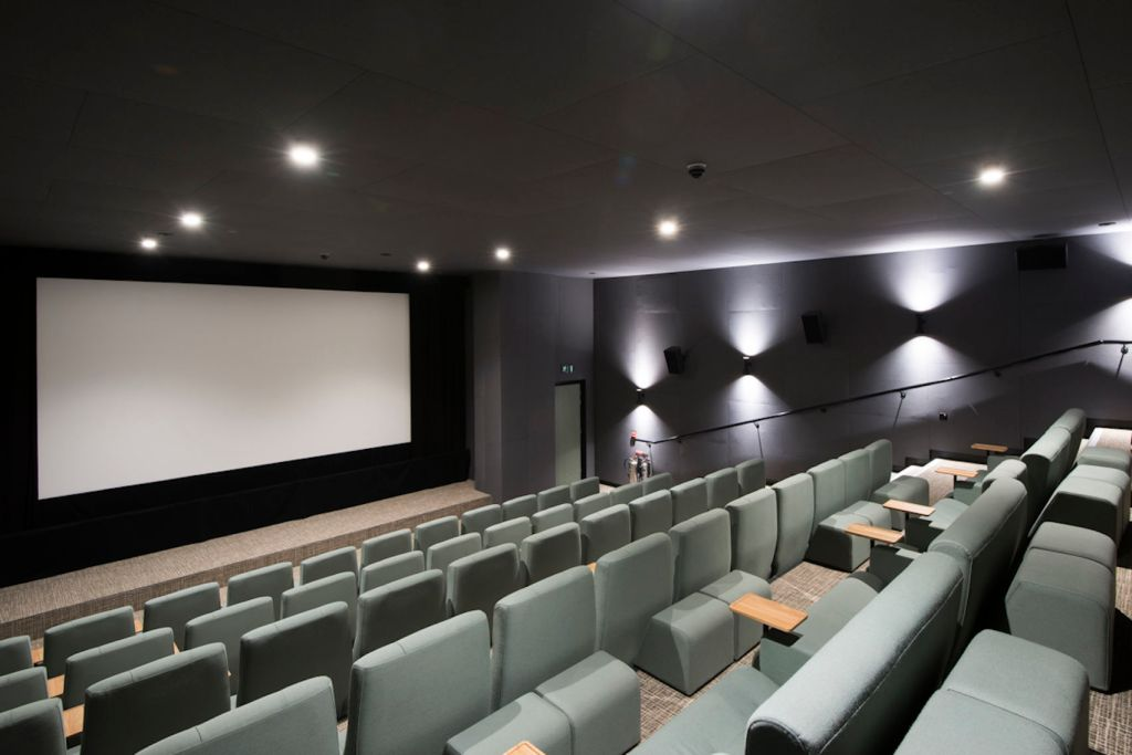 Screening room in London with mint green chairs and a large blank screen.