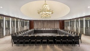 A large conference room with a square table in the middle