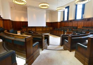 A council chamber room with dark wooden benches and high ceilings