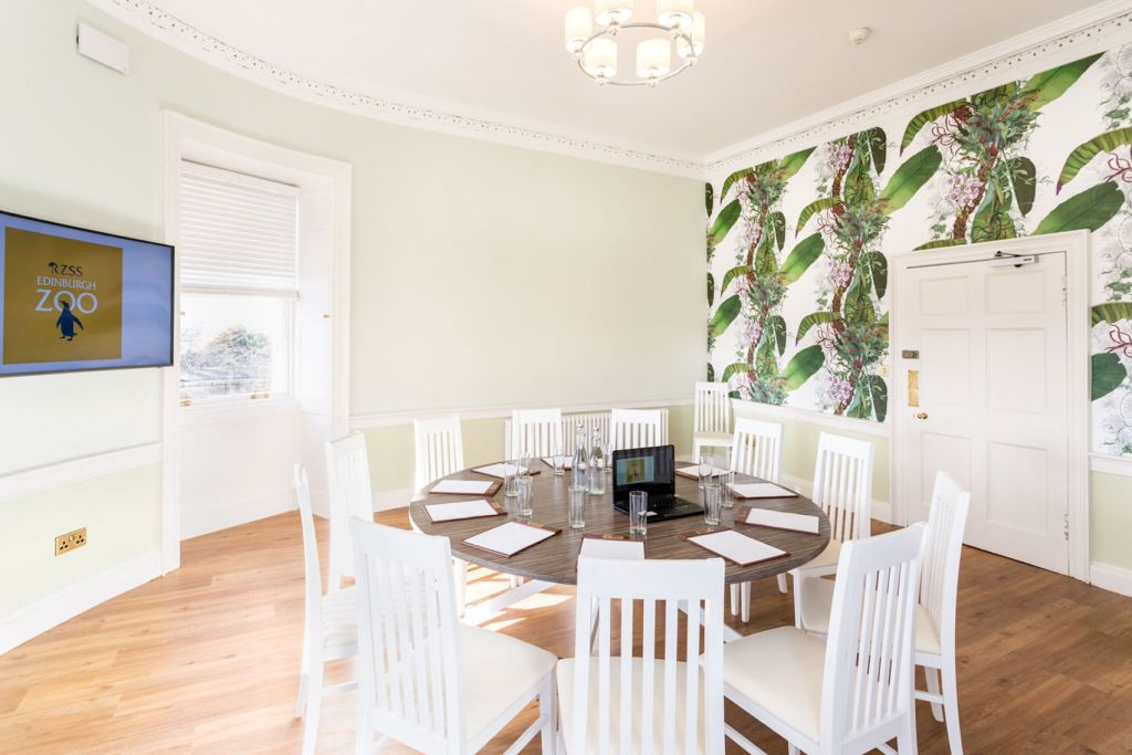 A meeting room at Edinburgh Zoo with 1 round table in the middle surrounded by white chairs