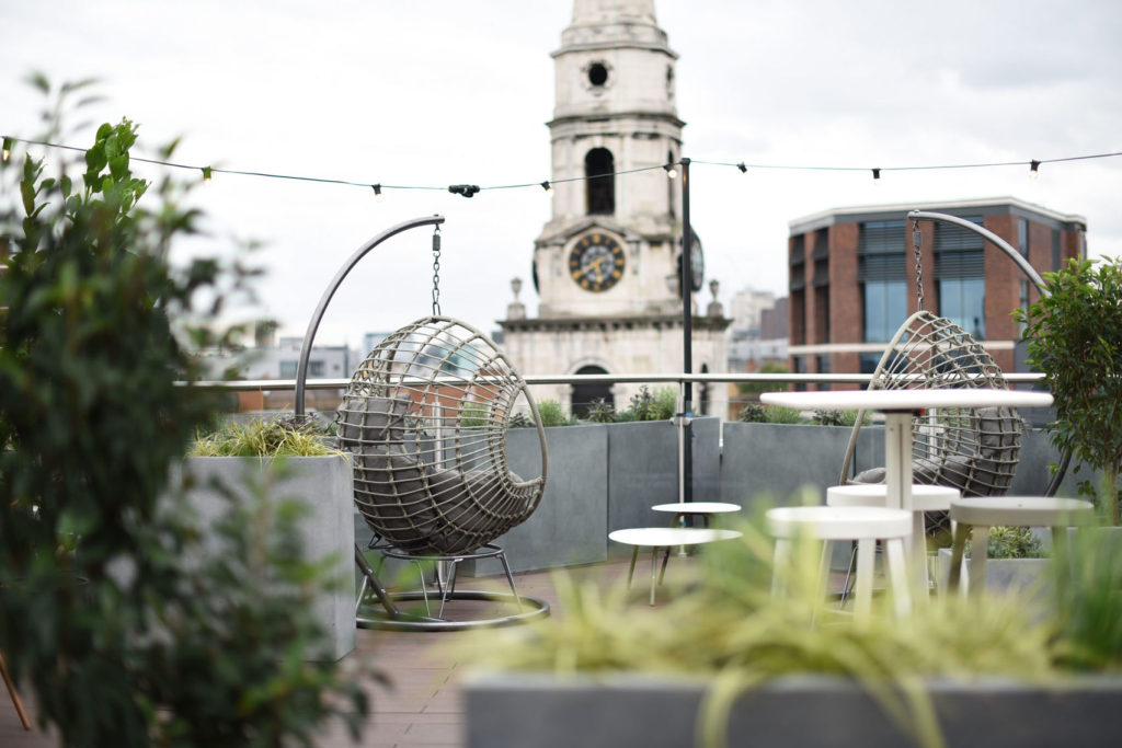 A rooftop bar with soft focus in the foreground and two swinging chairs in the background
