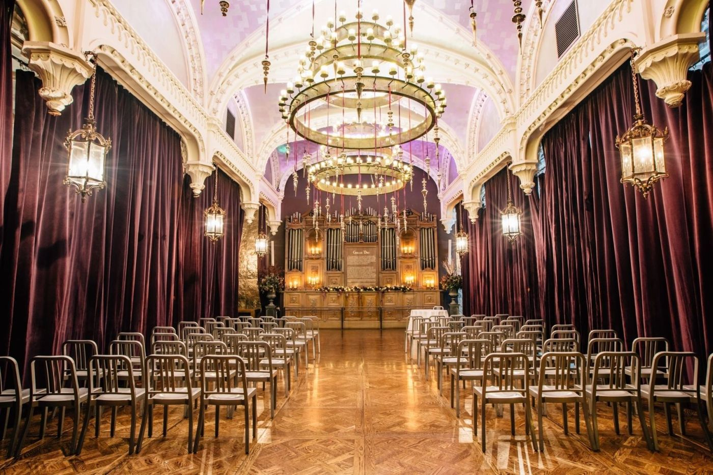 A large auditorium in Edinburgh. With high arched ceilings, red velvet drapes and chandeliers.