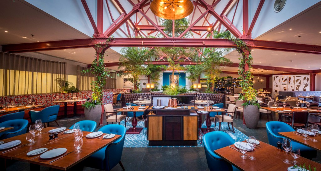 Bluebird is a venue in Chelsea that has blue chairs with red beams and lots of greenery