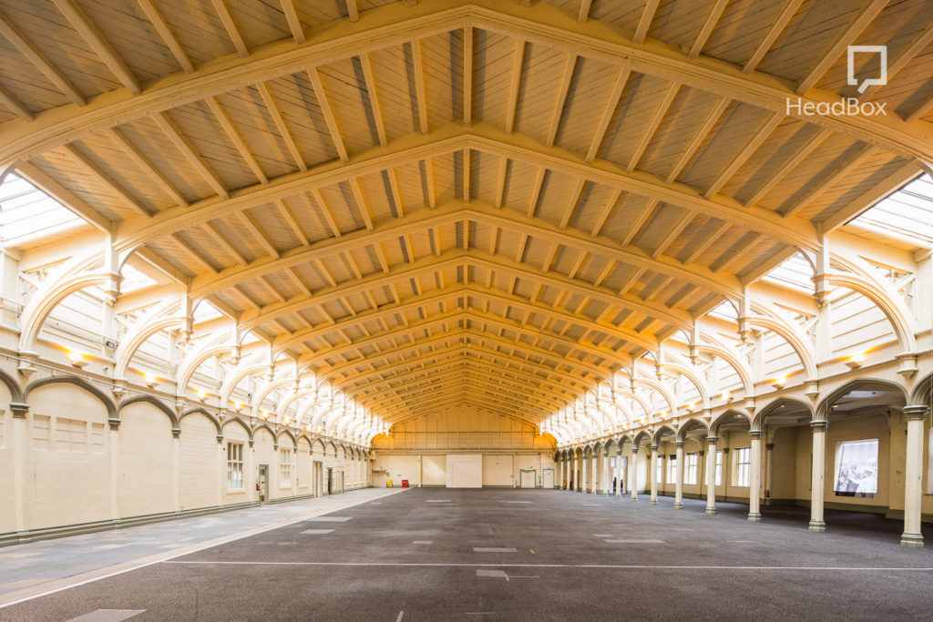 Large open warehouse space with arched wooden ceilings, natural light and concrete floor with pillars down each side