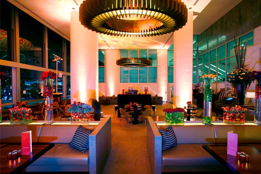 An event venue with high ceilings, sofas and a large circular light in the middle of the room.