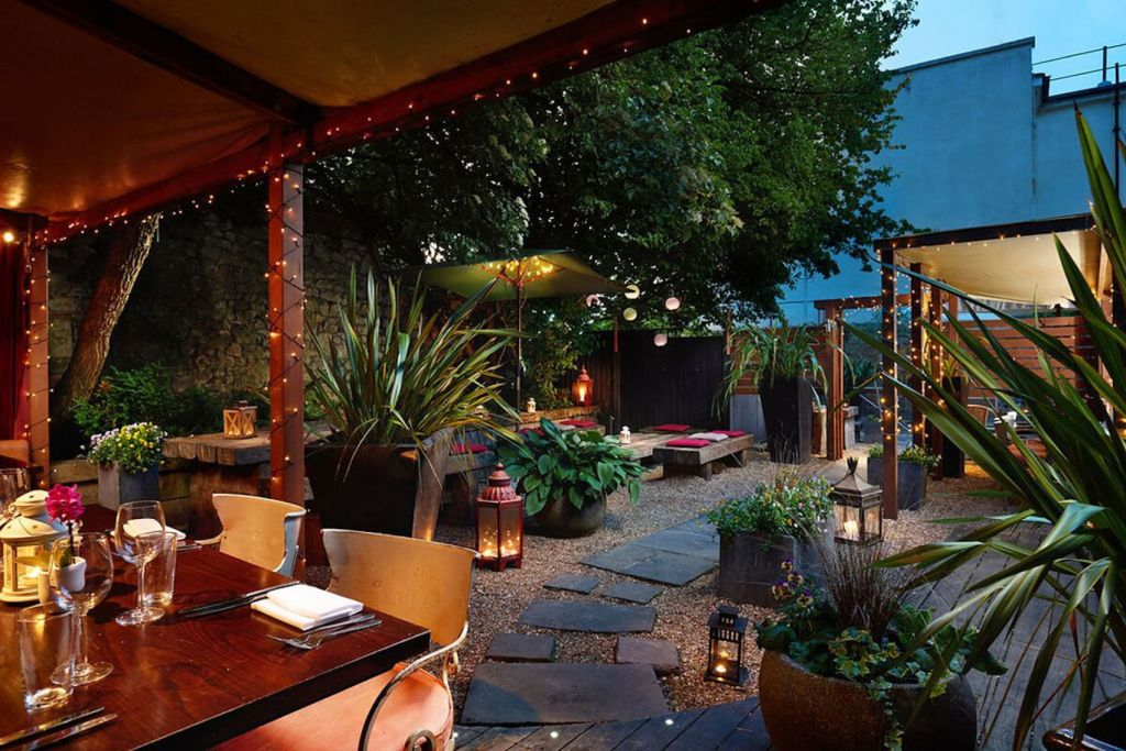 Garden area with fairy lights and wooden gazebo with dining tables, paving stones and plants