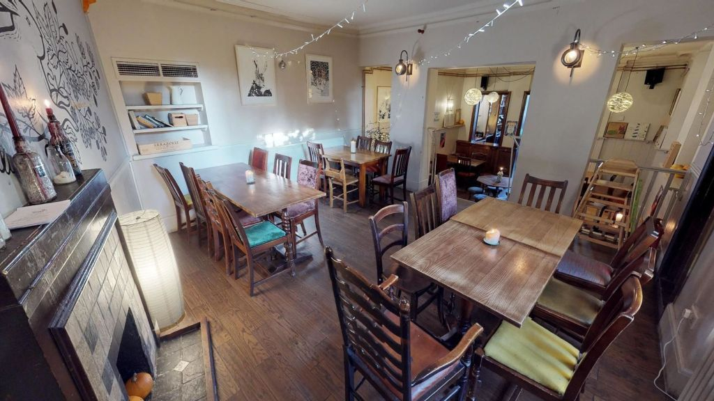 Intimate dining room with wooden tables and chairs, white lighting and fairy lights hanging from the ceiling