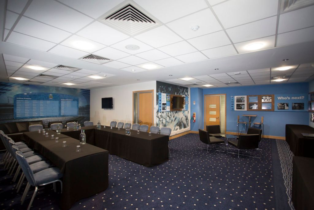 Large meeting room with tables set out in a u-shape and blue walls and carpeted floors
