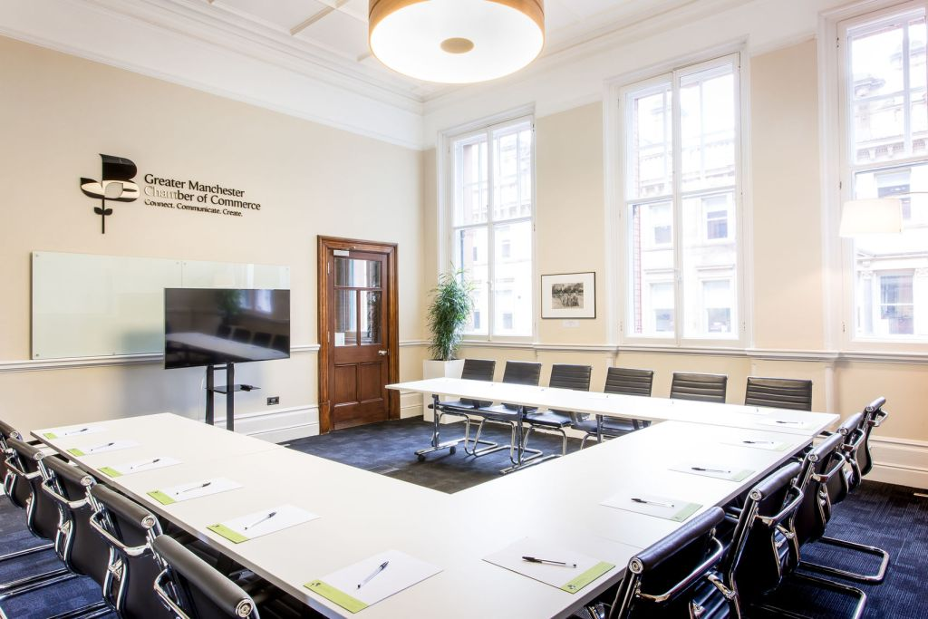 Large, bright meeting room with table and chairs in a u-shape facing a screen with windows offering natural light