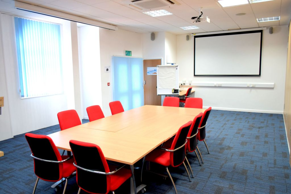 White-walled meeting room with rectangular wooden table and 10 red chairs on blue carpet