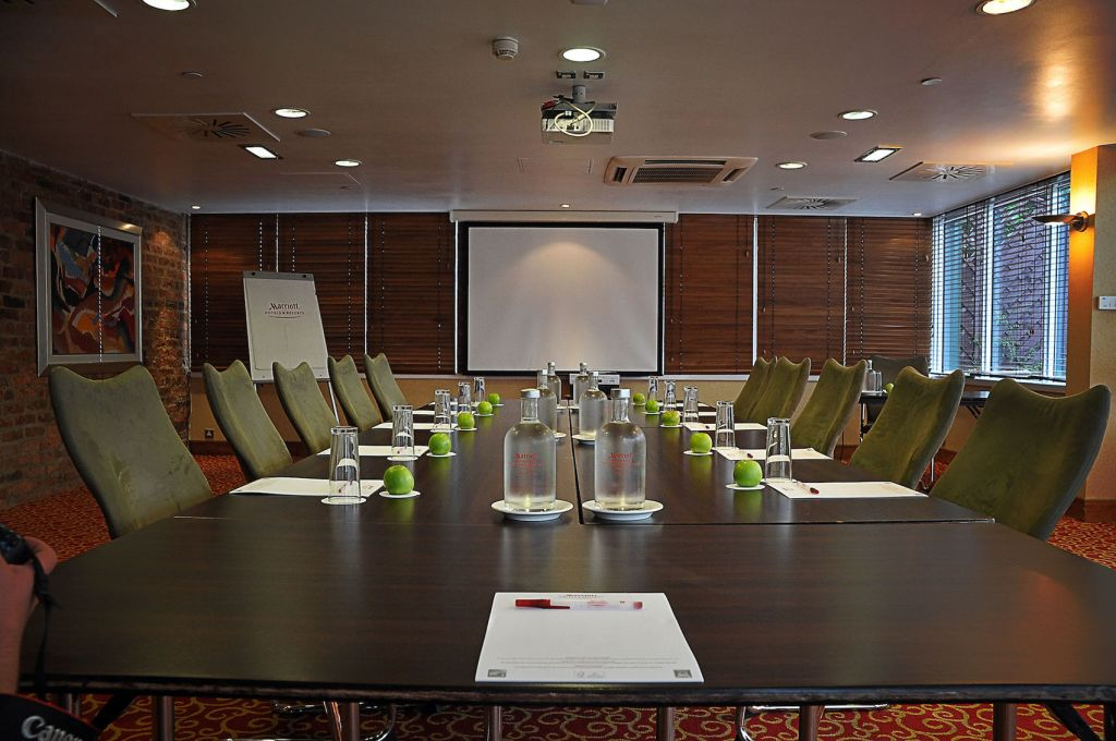 Large boardroom with long wooden table and screen on the wall with glasses and apples on the table